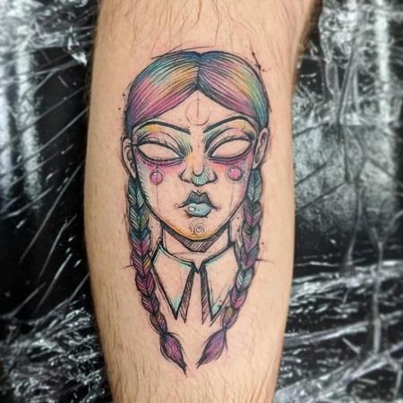 Tatuering av queer tatuerare Cynthia Sobraty. Demonperson med tomma ögon och flätor i regnbågsskimmer.