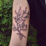 Tatuering på överarm av queer tatuerare Alex , nypongren i gravyr stil.