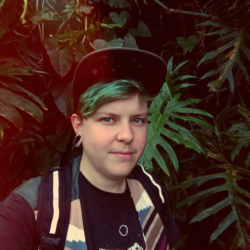 Självporträtt, fotografi av tatuerare Alex i grönt hår framför prunkande växter.