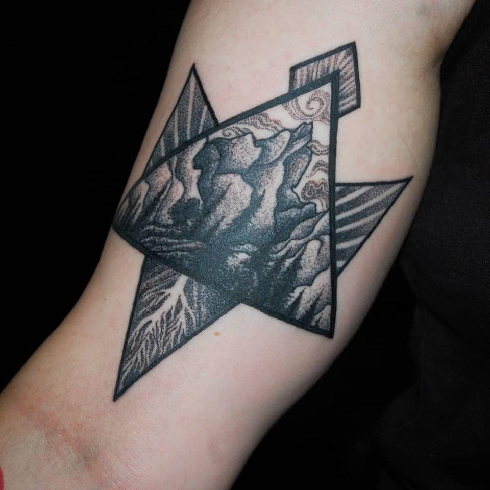 Geometrisk tatuering, trianglar med berg, rötter och engeristrålar. Tatuering i blackwork stil av tatuerare Soledad Aznar.