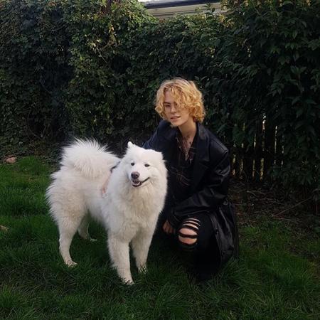 Leon sitter på huk i svarta kläder bredvid stor vit hund.