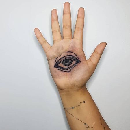 Svart öga i handflata, tatuering likt etsning av Leon på StaDemonia Tattoo.