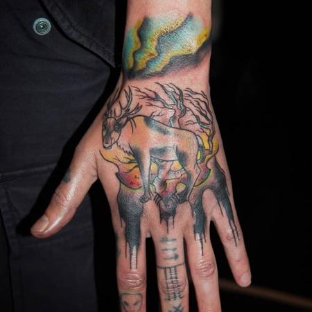 Ren med björk och norrsken som sällskap på hand och fingrar, tatuering i oldschool stil av Sara på StaDemonia Tattoo