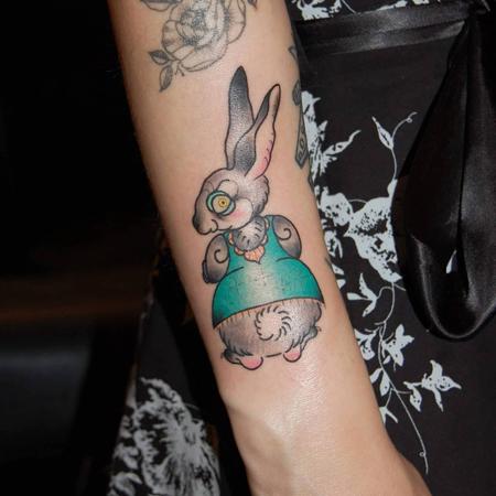 Liten galen kanin i grön klänning stirrar över axeln, tatuering i oldschool stil av Sara på StaDemonia Tattoo Stockholm
