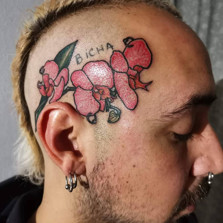 Orchideer sticker fram bakom öra, tatuering i oldschool stil av Soledad på StaDemonia Tattoo Stockholm