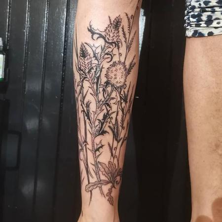 Tistlar och vilda blommor, trasslig tatuering i blackworkstil av Soledad på Stademonia Tattoo Stockholm