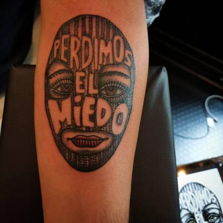 Feminin person med maskeringsluva och texten Perdimos el Miedo, tatuering i blackworkstil av Soledad på StaDemonia Tattoo Stockholm