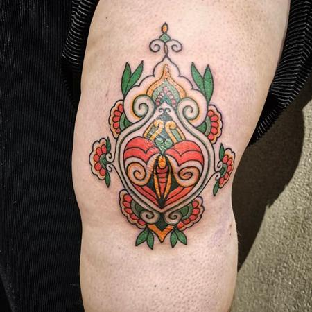 Ornamentalt knä i rött, gult och grönt, tatuering i oldschool stil av Soledad på StaDemonia Tattoo Stockholm
